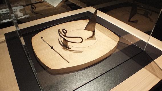 """Dies ist eines der Spielfelder Giacomettis - mit dem Titel """"Familie"""" (1931/1932). Zu sehen sind eine Frau, ein Segel und ein Kind. Die Rillen auf dem Brett regen den Betrachter dazu an, sich immer neue Positionen der drei Figuren im Geiste auszumalen. (Quelle: ndr.de)"""