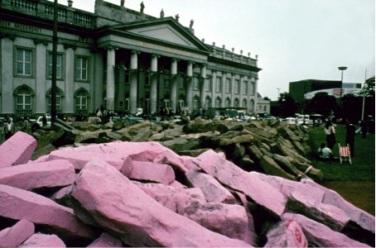 Eine Gruppe junger Männer sprüht im Juni 1982 einen Teil der Basaltsteine pinkfarben an (Fotonachweis: Stiftung 7000 Eichen (Hg.), 7000 Eichen. Joseph Beuys. Stadtverwaldung statt Stadtverwaltung (CD-ROM, Bilder), Kassel 2002)